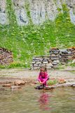 Girl washing hands in the river Stock Photo