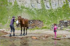 Man washing a horse. KETRISI, GEORGIA - JULY 17: Man washing a horse and a girl playing with water, Truso valley, Kazbegi. July 2017 stock photos