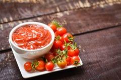 Ketschup in der Schale und in den frischen Tomaten auf weißem Platte Abschluss herauf Tomatensauce auf hölzernem dunklem Hintergr lizenzfreies stockfoto