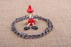 Kette um hölzerne Pinocchio-Puppe, die auf Segeltuch sitzt Lizenzfreie Stockbilder