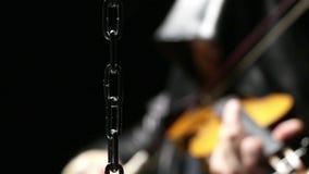 Kette und Mann, die auf einer Geige spielen stock footage