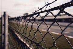 Kette-verbundener Zaun mit Stacheldraht oben mit Gras und Straße im Hintergrund Stockfoto