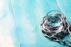 Kette wickelt ein Glas mit einem Alkohol ein Stockbilder