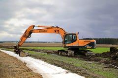 Kettenbagger Hyundais Robex 210LC-9 auf einem Feld am Frühling Stockfotografie