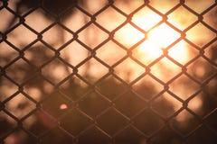 Kettenglied-Zaun mit Sonnenuntergang Hintergrund Lizenzfreie Stockfotos