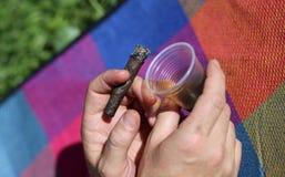 Kettenraucher mit Zigarre in der Hand und Glas Alkohol Lizenzfreie Stockfotografie