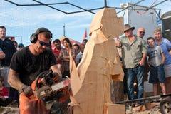 Kettensägen-Bildhauer-Creates Wooden Dog-Skulptur Stockfotografie