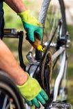 Ketting die van de mensen de smerende fiets voor het nieuwe seizoen handhaven royalty-vrije stock foto's