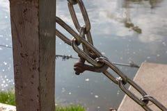 ketting en slot bij zonnige rivieroever stock fotografie