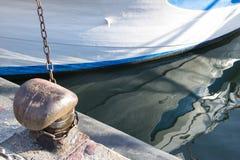 Ketting op een meerpaal wordt gebonden die Meertroskabel rond cleat op overzeese achtergrond wordt verpakt die Metaalkaapstander  Royalty-vrije Stock Fotografie