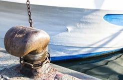 Ketting op een meerpaal wordt gebonden die Meertroskabel rond cleat op overzeese achtergrond wordt verpakt die Metaalkaapstander  Royalty-vrije Stock Foto's