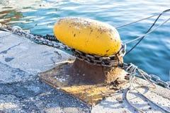 Ketting op een meerpaal wordt gebonden die Meertroskabel rond cleat op overzeese achtergrond wordt verpakt die Metaalkaapstander  Royalty-vrije Stock Foto