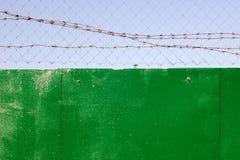 Ketting-verbinding en prikkeldraad bovenop groene omheining royalty-vrije stock fotografie