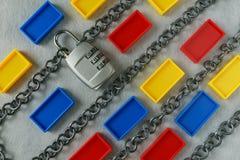 Kettingen met combinatiehangslot en kleurrijk plastic blok als sa stock fotografie