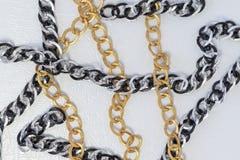 Kettingen op witte leerachtergrond Zilveren en gouden kleurenketens royalty-vrije stock fotografie