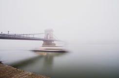 Kettingsbrug over de Donau en een boot, Boedapest, Hongarije, in mist, die lichten gelijk maken Stock Afbeelding