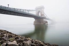 Kettingsbrug over de Donau en een boot, Boedapest, Hongarije, in mist, die lichten gelijk maken Royalty-vrije Stock Foto's