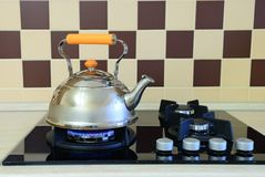 Kettle basking in the modern gas stove Royalty Free Stock Photography