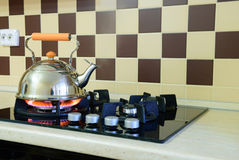 Kettle basking in the modern gas stove Royalty Free Stock Photos