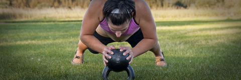 Kettle bell push-up. Photograph of a healthy young female doing a push-up in a panoramic view stock images