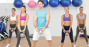 Kettle bells instructor leading a happy class of women Stock Photo