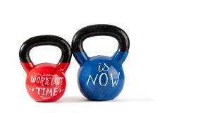 Kettle bells with motivational lettering. Red and blue kettle bells with motivational lettering Workout Time is Now isolated on white background with copy space stock images