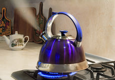 Kettle of boiling water on the flame of the gas stove. royalty free stock image