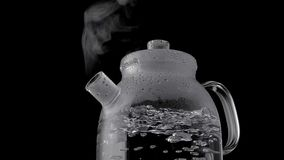 Kettle with boiling water and steam isolated on black background royalty free stock image