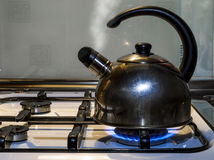 The kettle boils and releases steam on a gas stove Royalty Free Stock Photography