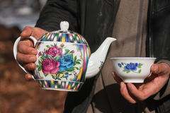 Kettle and a bowl in his hands. Tajik porcelain teapot and bowl in hands. Traditional national custom treats tea in Central Asia. Tajikistan Royalty Free Stock Photo