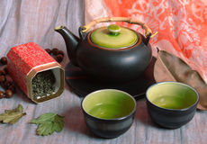 Kettle and bowls with tea Stock Image