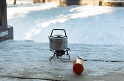 Kettle on the camp burner against the snow background. Equipment for the camp in real field winter conditions stock photography