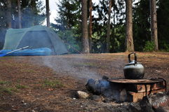 Kettle on campfire. Camping site in the forest with a kettle on a campfire royalty free stock photo