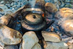 Kettle on campfire. A sooty kettle standing on the campfire surrounded by rocks stock photo