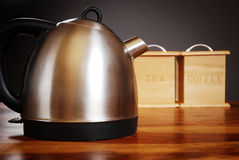 Kettle and canisters. A modern kettle and tea/coffee canisters on a wooden surface in front of a dark background royalty free stock image