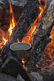 Kettle on charcoal, burning logs. The boiling army kettle on charcoal, burning logs Royalty Free Stock Photos