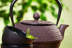 Kettle and closeup fresh mint leaves Royalty Free Stock Images