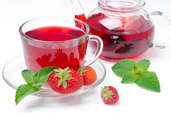 Kettle and cup of red tea with strawberries and mint on a white Royalty Free Stock Photography