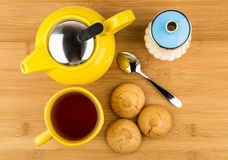 Kettle and cup of tea, sugar and biscuits on table Royalty Free Stock Images