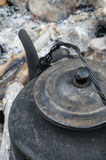 Kettle on the fire. Cover sooty kettle on the ashes Stock Photos
