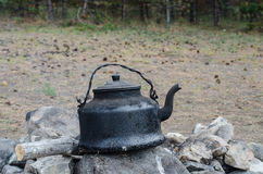 Kettle on the fire. Cover sooty kettle on the ashes Royalty Free Stock Image