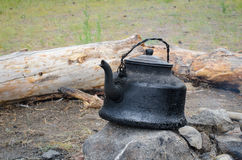 Kettle on the fire. Cover sooty kettle on the ashes Royalty Free Stock Photo