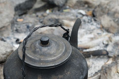 Kettle on the fire. Cover sooty kettle on the ashes Stock Photo
