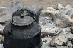 Kettle on the fire. Cover sooty kettle on the ashes Stock Image
