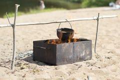 Kettle on a fire. On sand stock photos