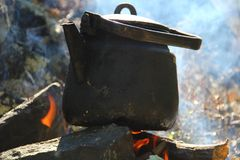 The kettle on the fire on the stones royalty free stock images