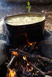 Kettle with food on campfire Stock Photography