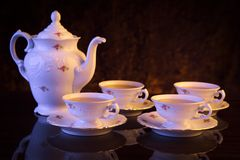 Kettle with four cups of tea on black background Stock Images