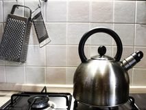 Kettle on a gas stove and grater on the wall royalty free stock images