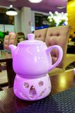 The kettle is heated by the candle on the table in lilac tones. On the background of the interior of the cafe Stock Photography